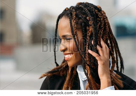 Shy African American female. Happy model smile. Young black woman smiling in selective focus outdoors, fashion hairstyle, happiness concept