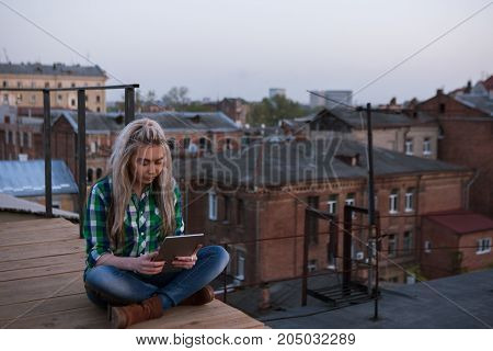 Freelance work outdoors. Modern girl on roof. Social media communication, gadget addiction , stylish female with tablet in focus on foreground, urban background