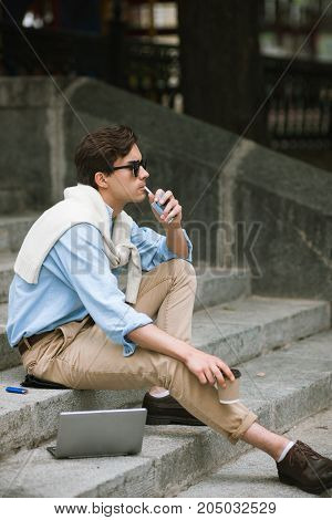 Young man with bad habits. Modern smoking youth. Unhealthy lifestyle, businessman on coffee break on urban background