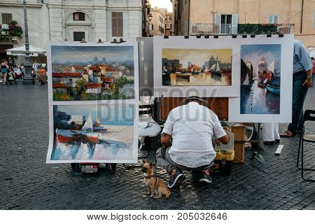 Rome, Italy - August 20, 2016: Painter selling his paintings in Piazza Navona in Rome.