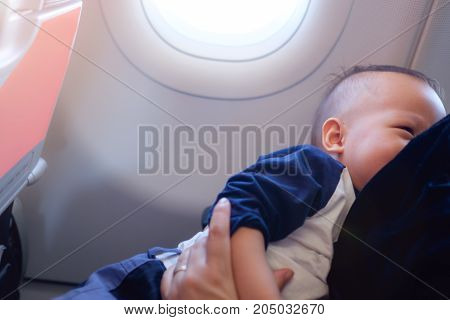 Asian mother is breastfeeding Cute little Asian 18 months toddler baby boy child on AirplaneToddler lying on mother's laps BreastFeeding in Public concept