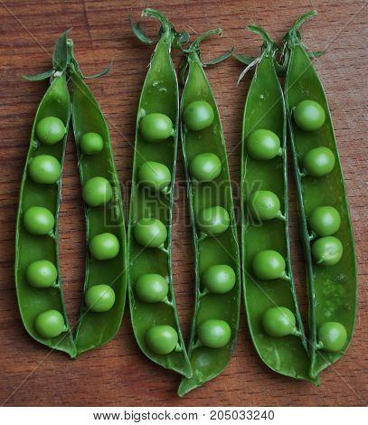 Open green peas in pods on wooden board