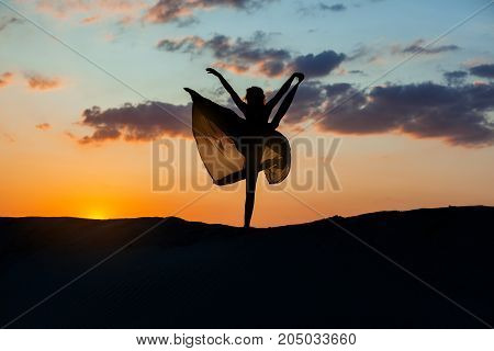 Dancer at sunset against the sky her dress fluttering. The backlight of the sun only contours of the figures are visible.