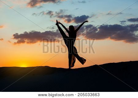 Woman is dancing at sunset against the sky. The backlight of the sun only contours of the figures are visible.