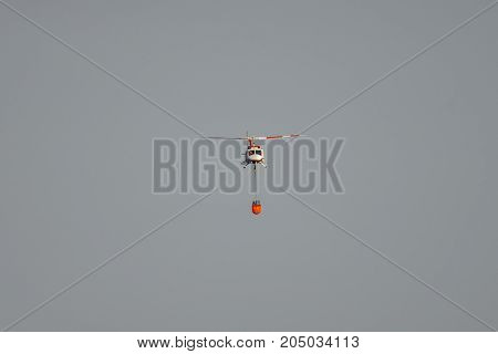 Long shot of helicopter with water tank flying against sky