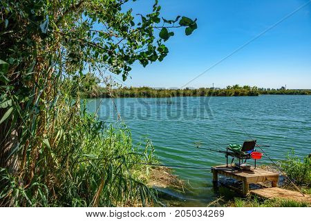 Wide angle view of lake and fishing chair with many rods