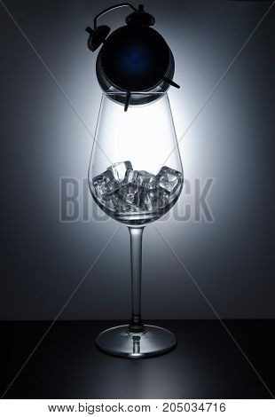 Wine glass filled with ice cubes and standing on the clock in the shade