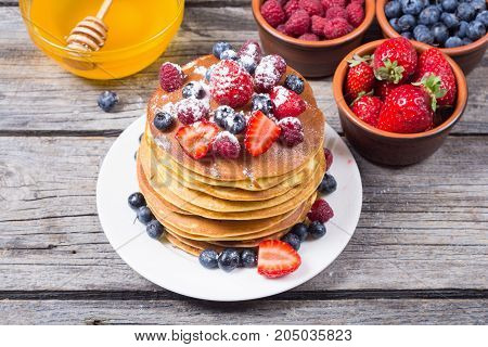 Pancakes with honey berries : blueberries raspberry and strawberry .