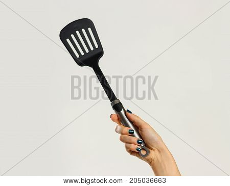 Female Hands Holding A Spatula For Frying. Isolated On Gray Background. Closeup