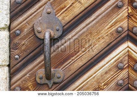 Antique door knob over a rusty wooden door. Horizontal