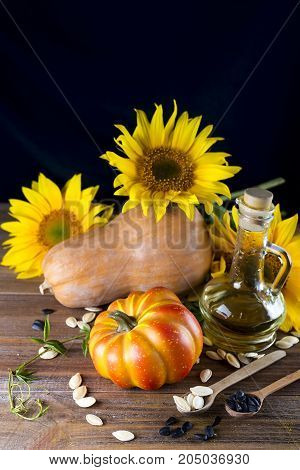 Autumn still life with pumpkins, oil and sunflowers on wooden background copy space