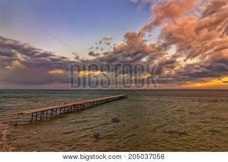 Old broken bridge in the sea sunrise shot