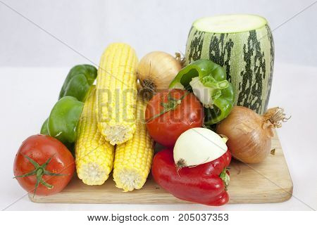 A bunch of vegetables and fruits including tomato Zucchini, Courgette, on the white background with green leafs