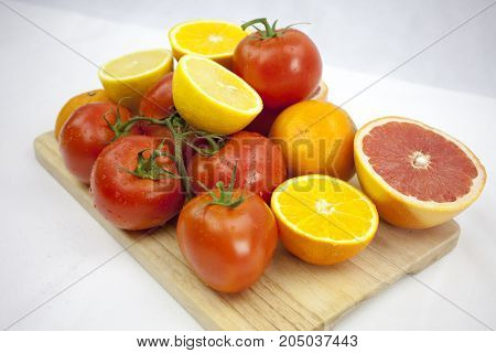 Juicy tomato and orange on the white background with green leafs and droops on the chopping block with copy space