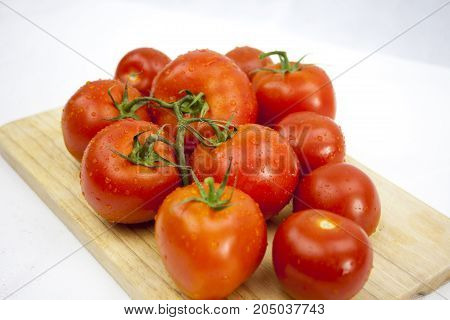 Juicy tomato on the white background with green leafs and droops  on the chopping block with copy space