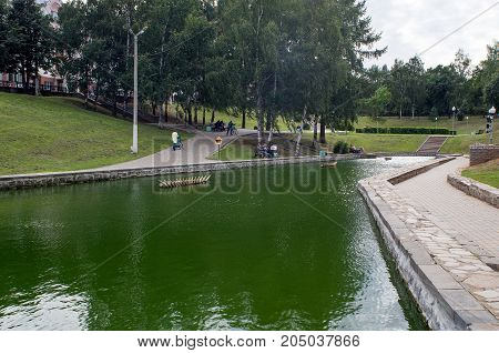 City Park recreation area with an artificial pond and paved alleys where the people strolling on a cloudy summer day.