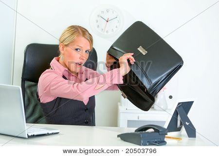 Shocked modern business woman sitting at office desk and searching something in briefcase