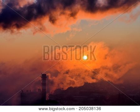 Smoking smoke stack at sunrise in the morning