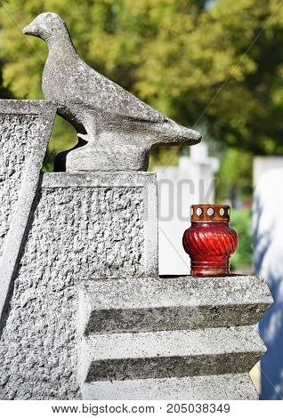 Dove and lantern on the tombstone in the public cemetery