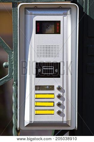 Intercom on the metal door outdoor in summer