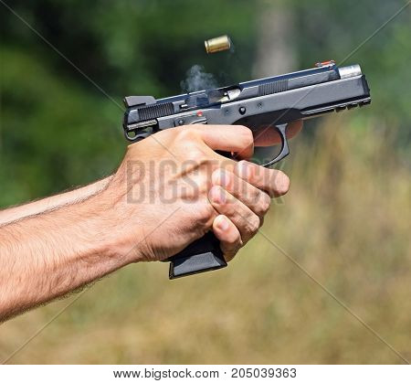 Shooting with a handgun outdoor in summer