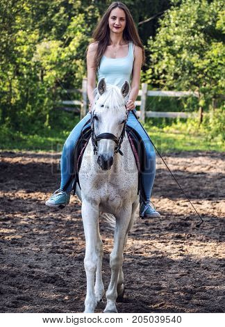 A beautiful girl is riding a white horse. Looking forward.