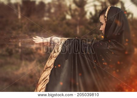 An enchantress in the woods, the witch in a black cloak uses magic