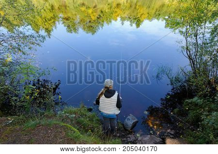 A fisherman woman stands with a fishing rod on the lake shore. In the water, reflections of trees from the opposite bank are visible.