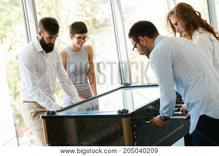 Coworkers playing table football together on break from work