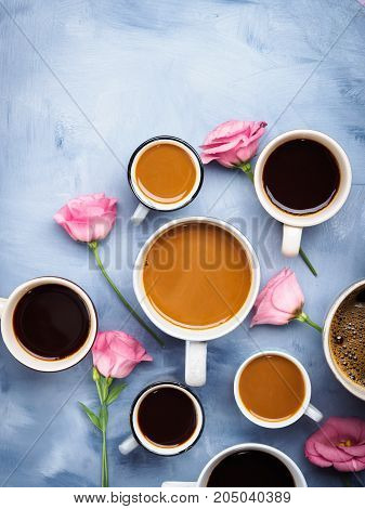 Group of Cups and mugs of coffee and pink flowers on blue background. Flat lay still life