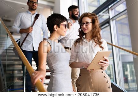 Portrait of two young attractive businesswomen talking on break from work