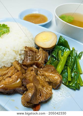 Stewed pork on rice isolated on white background. closeup