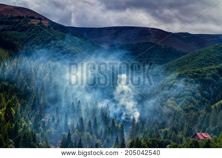 Smoke in a ravine of mountains in the Carpathians covered with rain clouds.