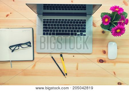 Work space of computer laptop and office supplies on wooden table desk. Top view concept