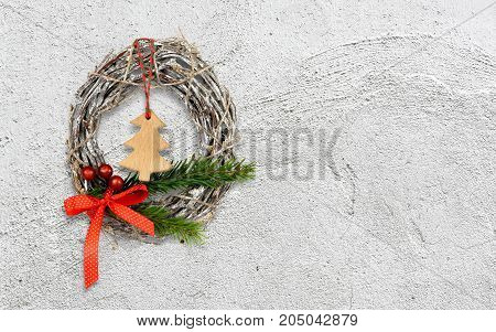 Christmas wreath decoration on white rough stucco wall