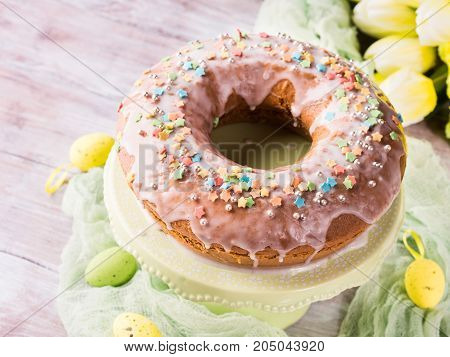 Easter bundt ring cake with sugar frosting sprinkles decorations eggs on wooden table background. Festive holiday home made treat and yellow flowers