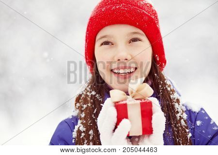 Pretty teenage girl with a gift in her hands. adolescent winter outdoors