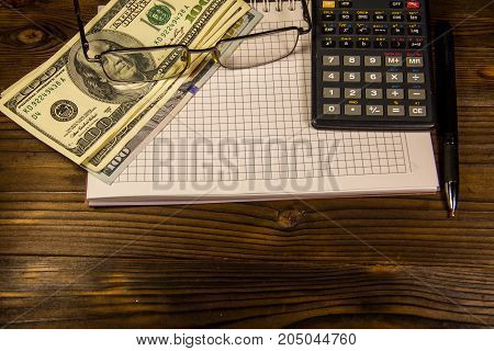 Notebook With Dollars, Pen, Glasses And Calculator On Wooden Desk