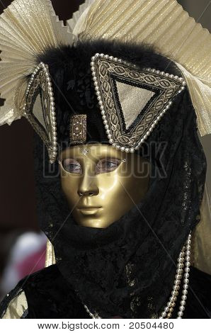 A portrait of one of the most beautiful masks photographed in open street during venetian carnival. poster