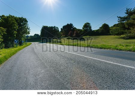 Empty Asphalt Country Road Passing Through Green Fields And Forest. Countryside Landscape On Sunny D