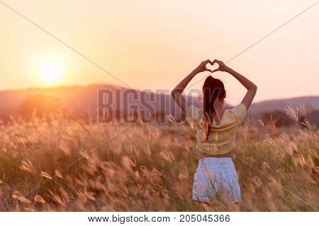 Girl Making A Heart-shape With Her Hands With Mountain Landscape In The Background.
