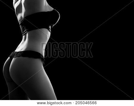 beautiful tan female body in lingerie on black background with copy space, monochrome