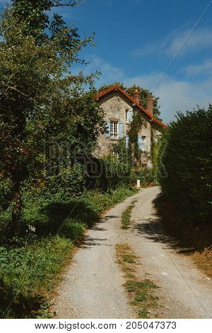 Old Country House With Blue Shutters And Gravel Road In Normandy, France On A Sunny Day. Beautiful C