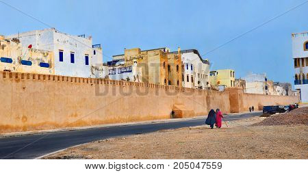 view of an old part of the Moroccan Medina behind which high fortifications tower buildings of a historical part of the city. In the forefront of the woman in traditional clothes