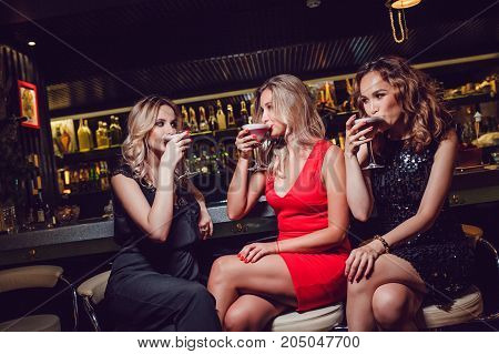 Beautiful women are sitting on the bar and drinking cocktails.