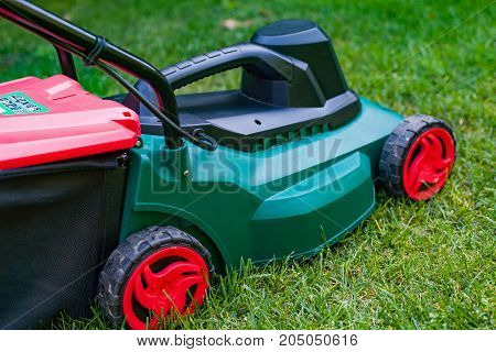 Close up modern lawn mower on the grass in the backyard