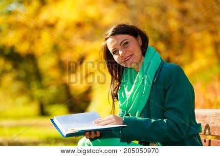 Woman enjoying beautiful autumn nature weather reading book sitting on bench in park during sunny autumnal day