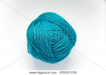 Small colorful ball of wool yarn on a white background. Hand craft supplies.
