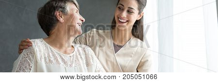 Caregiver Hugging Smiling Elderly Senior