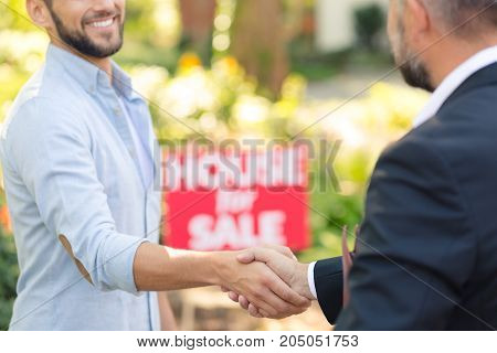Close-up of professional house seller in suit shaking hand of buyer of a new home